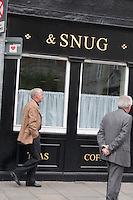 Two men walking past Peter's Pub in Dublin Ireland