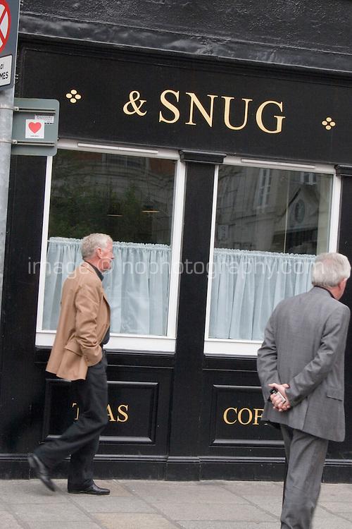 Two men walking past Peter's Pub in Dublin Ireland