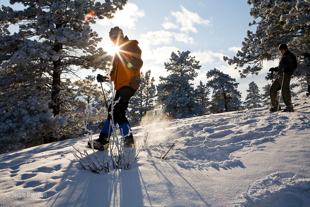 A couple of people are snowshoeing in the afternoon in Boulder, Colorado after a fresh snowfall.