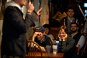 Audience members Spencer Shadel and Michelle Lindblom laugh at a story told by Dave Babler at the Johnson Public House Story Night, Friday, September 26, 2014
