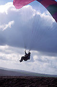 A man paragliding, on a cliff top, UK 2004