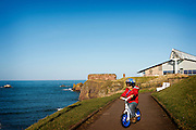 JMW toddler in red jacket and blue helmet on bike rides along coastal footpath in Dunbar, green grass, leisure centre in background, blue sky and blue sea