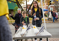 Kolby White challenges Gabrijela Djuric to a duck race at the LHS Key Club table during Pumpkin Fest Saturday afternoon.  (Karen Bobotas/for the Laconia Daily Sun)