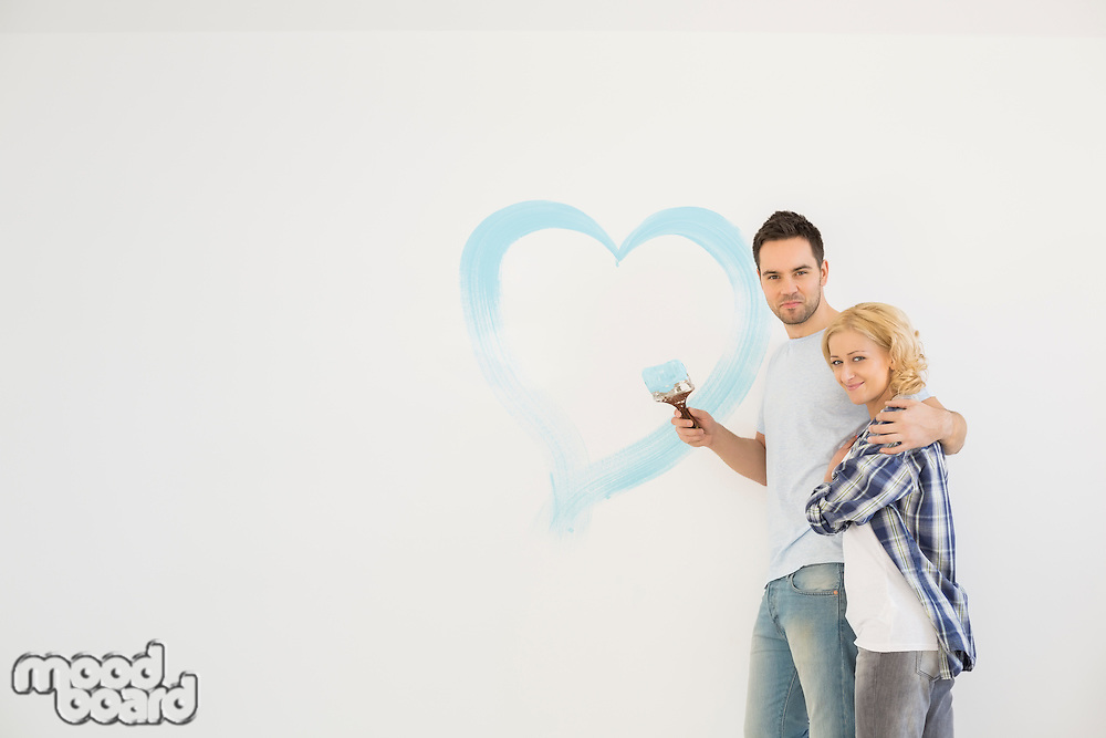 Portrait of loving mid-adult couple with painted heart on wall