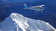 1963 Cessna 182F flying over Mt. Hood.