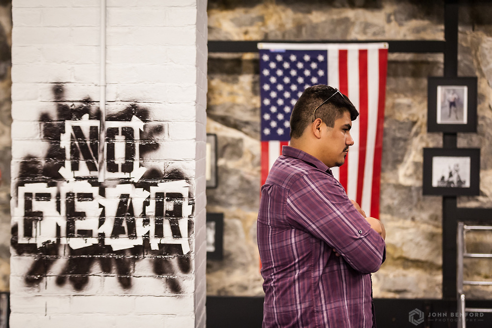 MPAL program alumnus and boxing coach Gibran Ortiz-Perez stands in front of the American flag during the reveal ceremony for the 2016 Building on Hope project at the Michael Briggs Community Center / Manchester Police Athletic League in Manchester, NH.