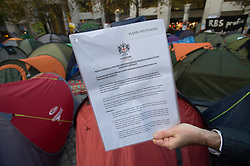 © Licensed to London News Pictures. 16/11/2011. London, UK. An eviction notice that was attached to a tent at the Occupy London camp today (16/11/2011). The City of London Corporation has told  activists to move by 6pm on Thursday or face legal action. Photo credit: Ben Cawthra/LNP