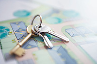 Key ring with three keys lying on architectural blueprint close-up
