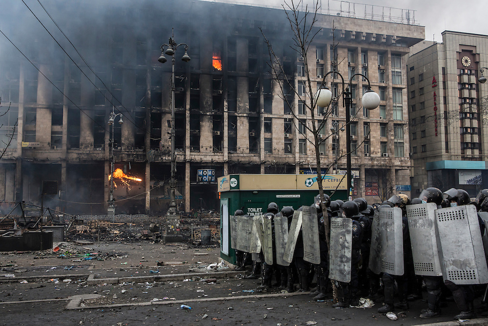 KIEV, UKRAINE - FEBRUARY 19: Police form a line against anti-government protesters on Independence Square as the Trade Unions Building, which served as the de facto headquarters of the protest movement, burns behind them on February 19, 2014 in Kiev, Ukraine. After several weeks of calm, violence has again flared between anti-government protesters and police as the Ukrainian parliament is meant to take up the question of whether to revert to the country's 2004 constitution. (Photo by Brendan Hoffman/Getty Images) *** Local Caption ***