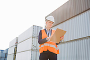 Female worker reading clipboard in shipping yard