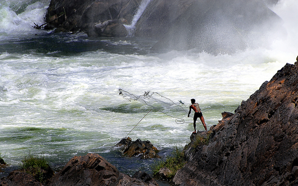 A fisherman trying his luck at Khone Papheng falls, Laos.