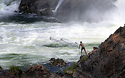 A fisherman trying his luck at Khone Papheng falls, Laos.