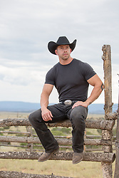 cowboy sitting on a rustic wooden fence on a ranch