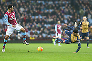 Arsenal's Alex Oxlade-Chamberlain is tackled by Aston Villa's Joleon Lescott during the Barclays Premier League match between Aston Villa and Arsenal at Villa Park, Birmingham, England on 13 December 2015. Photo by Shane Healey.