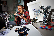"Japanese artist Hajime Sorayama in his studio, surrounded by the original design of AIBO, his drawings and KAWS x Hajime Sorayama Collaboration - ""No Future Companion"" silver figure (left) and Mickey (Right)"