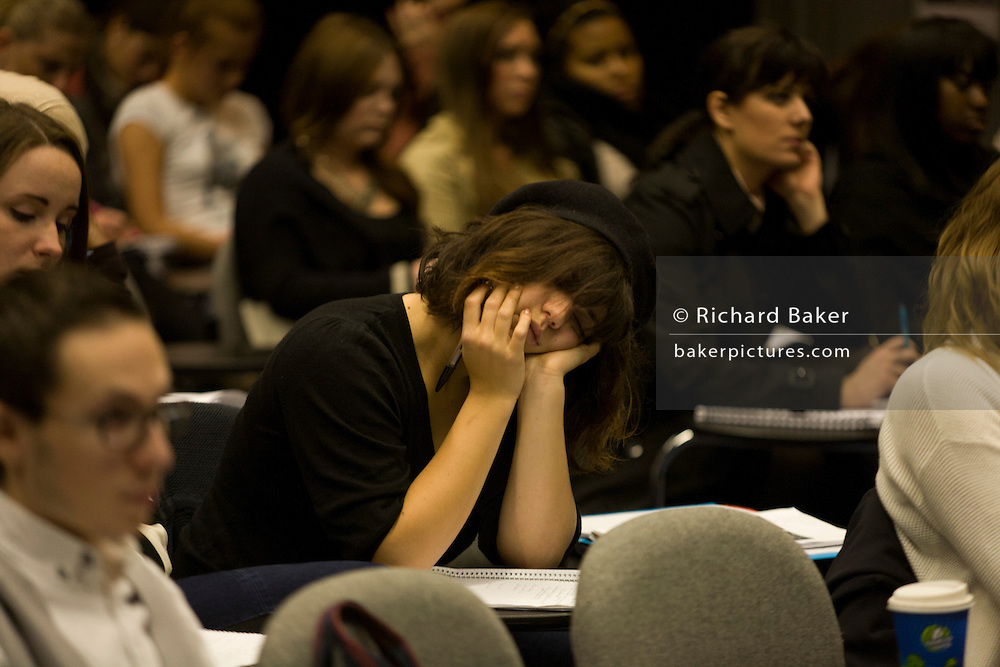 Tired girl student sleeps through lecture in Henry Thomas lecture theatre at London Metropolitan University.