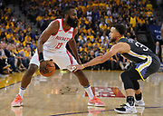 April 30, 2019; Oakland, CA, USA; Houston Rockets guard James Harden (13) dribbles the basketball against Golden State Warriors guard Stephen Curry (30) during the second quarter in game two of the second round of the 2019 NBA Playoffs at Oracle Arena.
