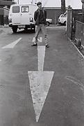 Boy standing next to arrow street markings, Ealing, UK, 1985.