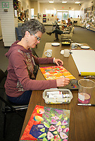 Wendy Wilson of Laconia works on a collage piece at the NH Open Doors in conjunction with Lakes Region Arts Association at the Tanger Outlet on Sunday afternoon.  (Karen Bobotas/for the Laconia Daily Sun)
