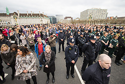 Westminster, London, March 29th 2017. Police officers, members of the emergency services and a large contingent of Muslims from across the UK as well as members of the public march across Westminster Bridge, exactly a week after the terror attack. PICTURED: The crowd stays silent as the victims are remembered.