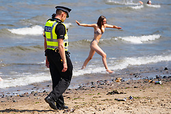 Edinburgh, Scotland, UK. 31 July, 2020. Temperature of 25C and sunshine brought huge crowds to Portobello Beach outside Edinburgh. Several large groups of teenagers were enjoying beach and alcoholic drinks were very popular. Pictured; Police patrolling the busy beach asked the young people to not drink alcohol in the sea. Iain Masterton/Alamy Live News