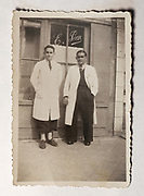 Photograph of the father of Pierre Pean and his clerk, outside his hairdressers in Sable-sur-Sarthe, Pays de la Loire, France, in 1941, during the Second World War. Pierre Pean, born 1938 in Sable-sur-Sarthe, is a French investigative journalist and author. Picture by Manuel Cohen