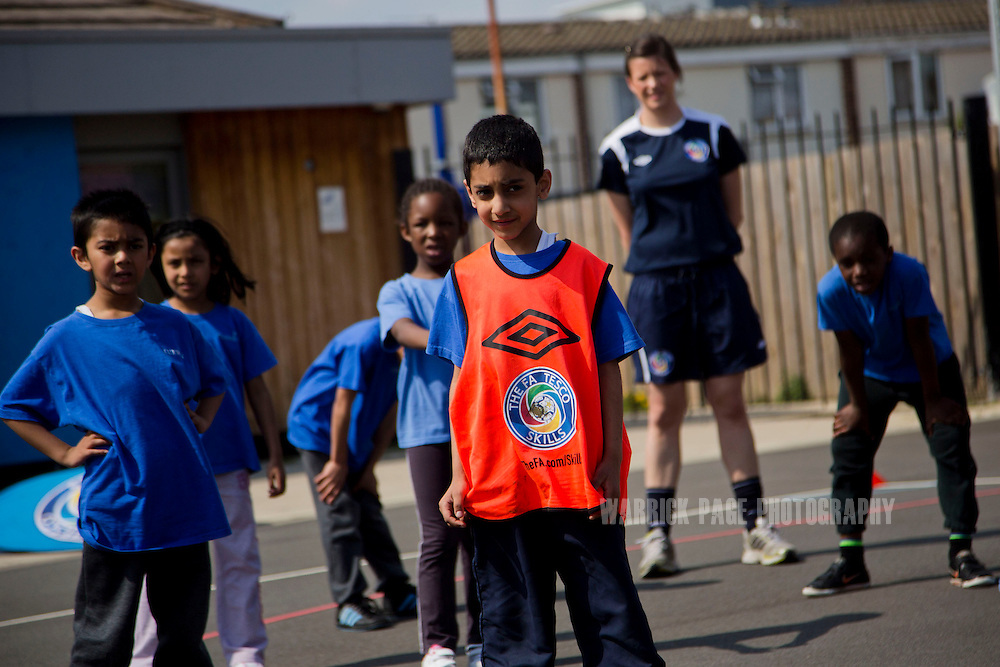 Year 2 students participate in football drills with coaches during a Tesco Skills Session at Curwen Primary School, on April 30, 2013, in Newham, England. (Photo by Warrick Page)