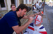 A young man has his face painted by a friend during 1995 VE Day 50th anniversary street party in London's East End. He sits with an outdoor party behind him in full swing that celebrates the 50th anniversary of VE (Victory in Europe) Day on 6th May 1995. In the week near the anniversary date of May 8, 1945, when the World War II Allies formally accepted the unconditional surrender of the armed forces of Germany and peace was announced to tumultuous crowds across European cities, the British still go out of their way to honour those sacrificed and the realisation that peace was once again achieved. Street parties now – as they did in 1945 – played a large part in the country's patriotic well-being.
