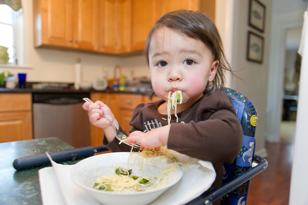 Girl with food in mouth, age 21 months old, feeding self in booster chair looking at camera