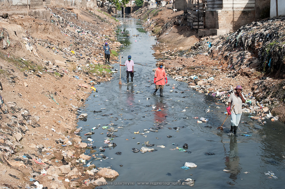 A severely polluted river divides east and west Nima, a densely populated area of Ghana's capital, Accra. Both sides of the community slope down to the river,  washing trash and debris into the watercourse when it rains. In addition, in the absence of adequate waste collection and sanitation, the river serves as a de facto dumping ground and a latrine. Sanitation workers regularly clear the waterway, but refuse is not collected, only raked to the banks to allow the water to flow.