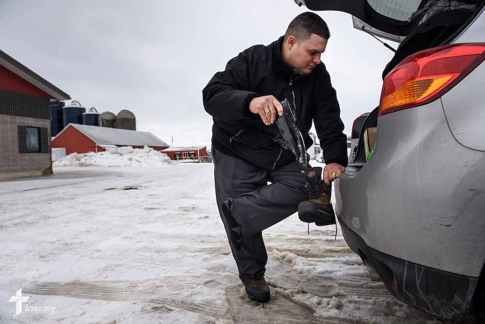 Vicar David Blas swaps dress shoes for boots at a dairy farm in rural Random Lake of Sheboygan County, Wis., on Thursday, Jan. 28, 2016. The missionary-at-large at LCMS Sheboygan County Hispanic Outreach and St. John's Lutheran Church of Plymouth, Wis., reaches out to Hispanic workers amongst the Hispanic population in the area. LCMS Communications/Erik M. Lunsford