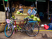 22 NOVEMBER 2017 - YANGON, MYANMAR: Workers put coconuts brought to Yangon on a river barge into a basket on a bike for delivery within Yangon.    PHOTO BY JACK KURTZ