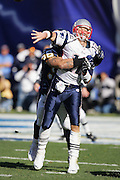 SAN DIEGO - JANUARY 14:  Quarterback Tom Brady #12 of the New England Patriots grimaces as he unloads a pass and gets hit by linebacker Shawne Merriman #56 of the San Diego Chargers at the AFC Divisional Playoff Game held on January 14, 2007 at Qualcomm Stadium in San Diego, California. The Patriots defeated the Chargers 24-21. ©Paul Anthony Spinelli *** Local Caption *** Tom Brady;Shawne Merriman