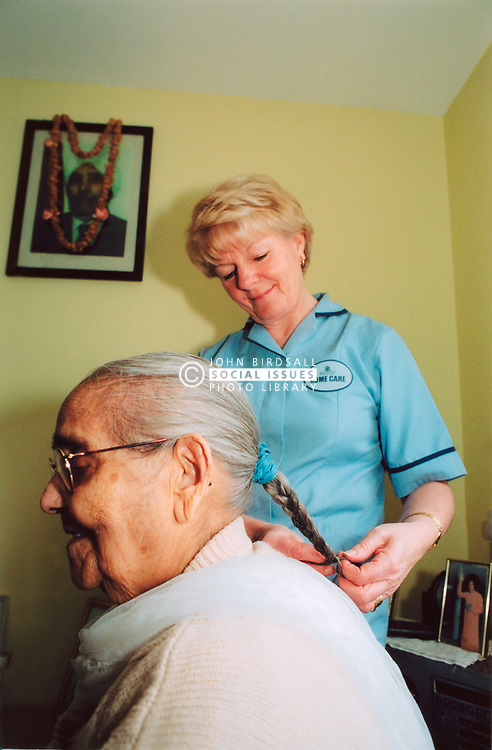 Home help in old peoples home; Yorkshire, Elderly Asian woman having her hair plaited, UK