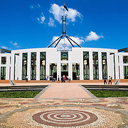 """The front of Parliament House, featuring an aboriginal tiled design on the ground. Parliament House is the meeting place of the Parliament of Australia. It is located in Canberra, the capital of Australia. It was opened on 9 May 1988 by Queen Elizabeth II, Queen of Australia.[1] Its construction cost was over $1.1 billion. At the time of its construction it was the most expensive building in the Southern Hemisphere. Prior to 1988, the Parliament of Australia met in the Provisional Parliament House, which is now known as """"Old Parliament House""""."""