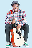 Portrait of a young African American man with guitar over light blue background