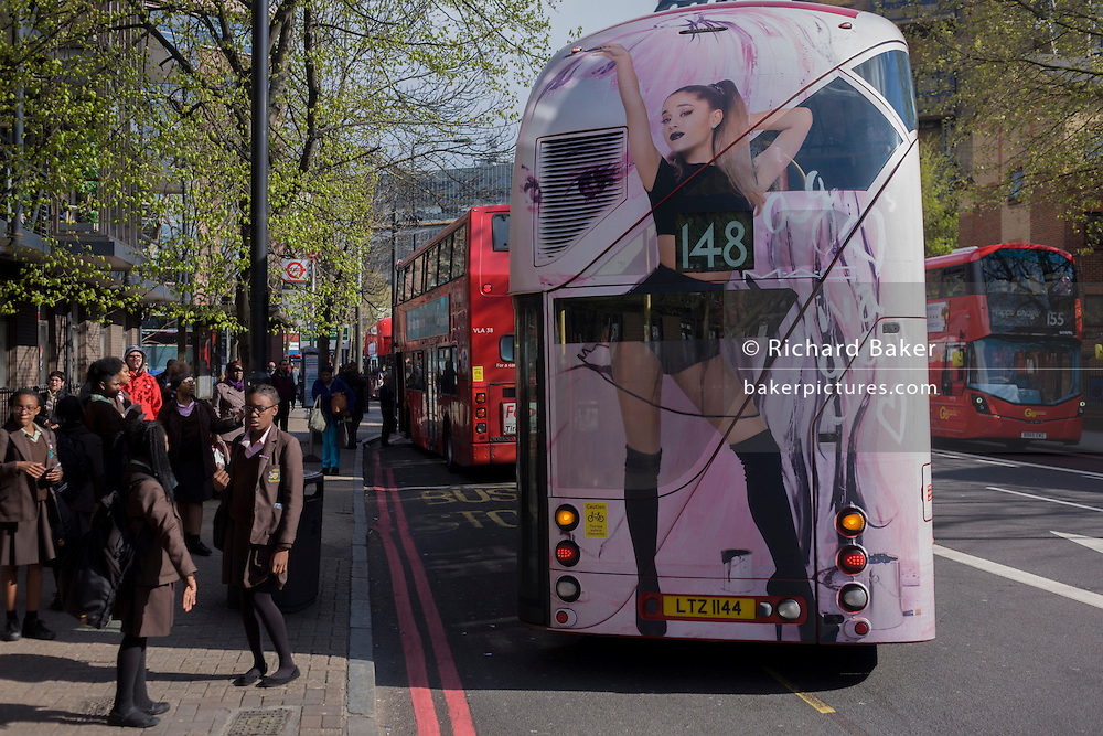 Schoolgirls wait for their buses as a Routemaster bus featuring an ad of sexuality pulls away towards Elephant & Castle in the south London borough of Lambeth.