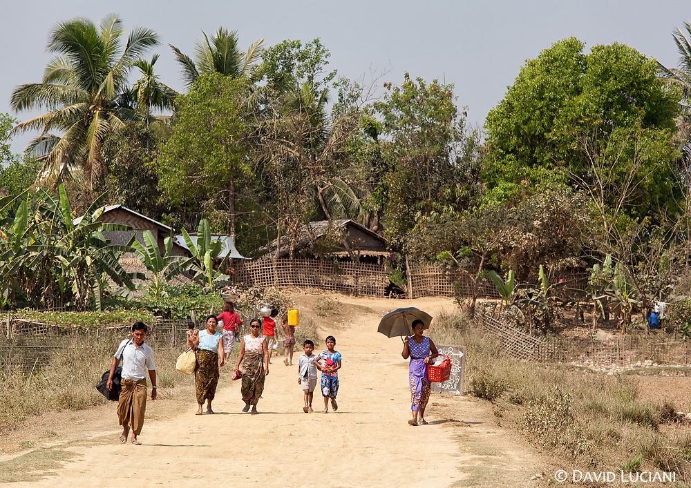 Local people walking from their villages on a road leading to the main temple area of Mrauk U.
