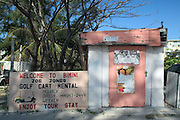 Signs advertising tourist services on a old building along the King's Highway in Alice Town on the tiny Caribbean island of Bimini, Bahamas