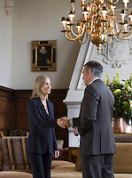 Business woman and man shaking hands under chandelier