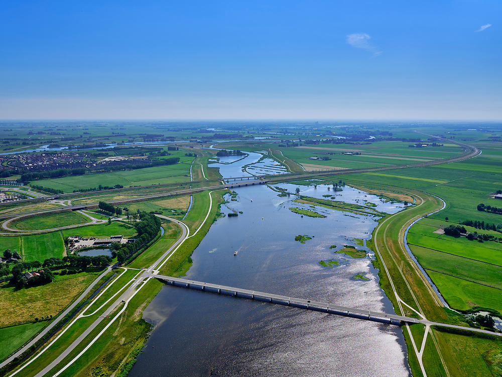 "Nederland, Overijssel, Gemeente Kampen; 21–06-2020; het Reevediep richting IJssel met  Nieuwendijkbrug in de voorgrond en gezien naar Reevediepbrug (rijksweg N50) en spoorbrug Reevediep. Voor de ze bruggen natuurgebied De Enk.<br /> Het Reevediep is aangelegd in het kader van het project Ruimte voor de Rivier om bij hoogwater water af te voeren voordat dit het nabij gelegen Kampen bereikt, direct naar het IJsselmeer, de 'bypass Kampen'. Het Reevediepgebied is ook een natuurgebied en vormt een ecologische verbindingszone tussen rivier de IJssel en Drontermeer.<br /> Reevediep in the direction of river IJssel, seen from the new Nieuwendijk bridge.<br /> The Reevediep has been constructed as part of the Room for the River project, and functions to discharge high waters before reaching the nearby Kampen, directly to the IJsselmeer, the ""bypass Kampen"". The Reevediep area is also a nature reserve and forms an ecological connecting zone between the river IJssel and Drontermeer.<br /> <br /> luchtfoto (toeslag op standaard tarieven);<br /> aerial photo (additional fee required)<br /> copyright © 2020 foto/photo Siebe Swart"