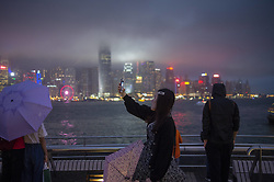 May 5, 2019 - Hong Kong, Hong Kong - A women (C) is seen taking a photo in-front of the skyline of Central District in Hong Kong, China. 5 May 2019. (Credit Image: © Vernon Yuen/NurPhoto via ZUMA Press)