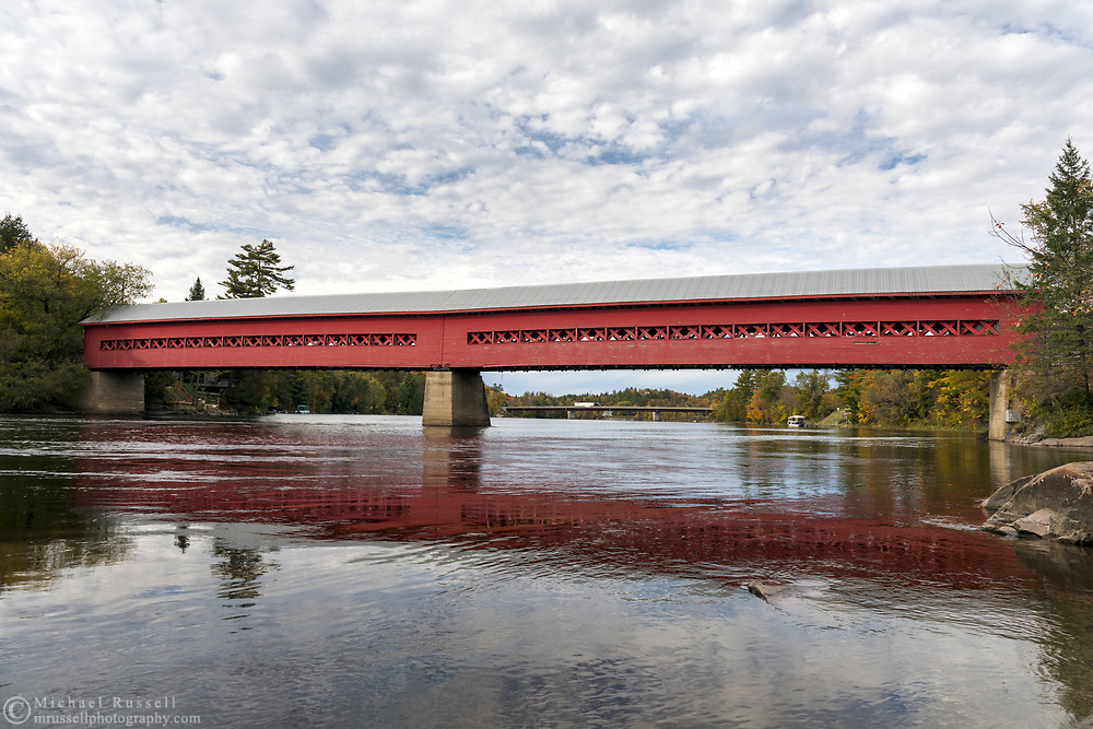 The Wakefield Covered Bridge over the Gatineau River in Wakefield, Québec, Canada.  Originally built in 1912, the covered bridge at this location burned down in 1984.  In 1997 this new bridge was completed where the original was located.