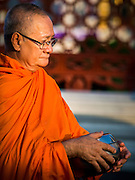 31 MARCH 2015 - BANGKOK, THAILAND: A monk at Wat Benchamabophit in Bangkok waits for Buddhist lay people to bring alms to the temple. Wat Benchamabophit Dusitvanaram, a Buddhist temple (wat) in the Dusit district of Bangkok, Thailand. Also known as the marble temple, it is one of Bangkok's best known temples and a major tourist attraction. It typifies Bangkok's ornate style of high gables, stepped-out roofs and elaborate finials. Monastic life at Wat Bencha differs from most other temples in that lay people come to the temple to present food and alms to the monks rather than the monks going out and walking through the community as they do at most other Thai temples.     PHOTO BY JACK KURTZ