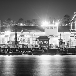 Newport Beach Balboa Fun Zone at night black and white panorama photo. The Balboa Fune Zone is a popular attraction along Newport Harbor in Orange County Southern California. Panoramic photo ratio is 1:3. Copyright ⓒ 2017 Paul Velgos with All Rights Reserved.