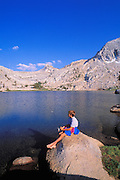 Boy fishing from a rock on the shore of Budd Lake, Tuolumne Meadows area, Yosemite National Park, California