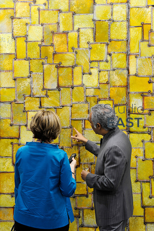 HONG KONG - MARCH 13:  An exhibitor explains in details the triptych 'Silksanroute' by Nathan Slate Joseph in art fair Art Central on its first day on March 13, 2015 in Hong Kong, Hong Kong.  (Photo by Lucas Schifres/Getty Images)