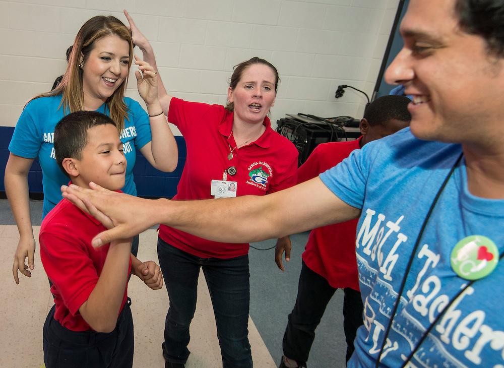 Principal Aaron Dominguez, right, and students participate in a pep rally to energize for STAAR testing at Garcia Elementary School, March 27, 2014.