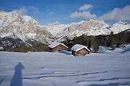 Mounts Lavarella and Conturines behind  snow covered wooden barns at the Alta Badia ski resort near Corvara The Dolomites, South Tyrol, Italy