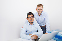 Portrait of businessmen with laptop at desk in office